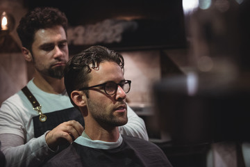 Barber putting cape over clients neck