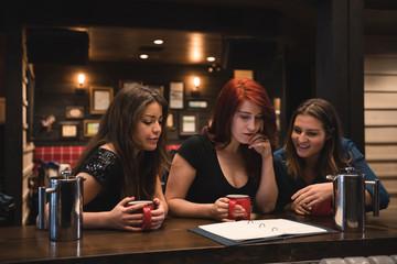 Friends looking at menu in bar