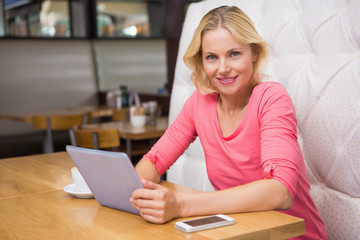 Woman having a coffee using tablet