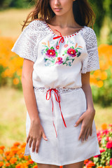 girl stands in the white mini dress with pattern of poppy in the field