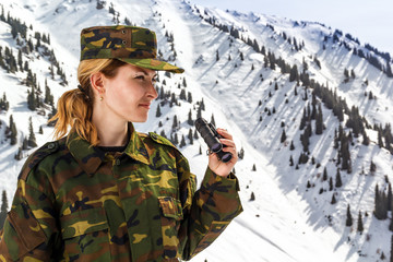 young woman in khaki uniform with binoculars on a background of snow-capped mountains