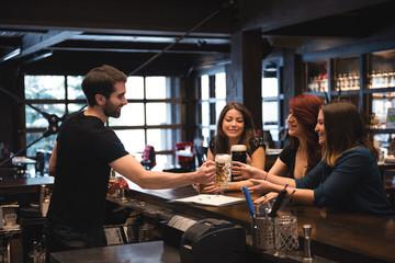Bartender serving beer at bar counter
