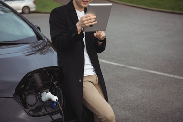 Man using digital tablet while charging electric car