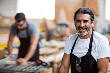 Happy carpenter standing in workshop