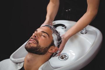 Smiling man getting his hair wash