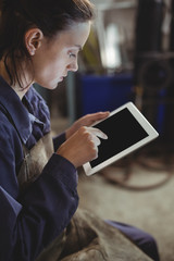 Female welder using digital tablet