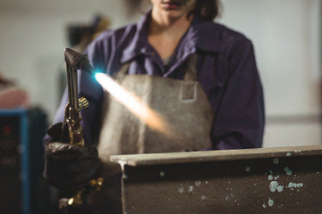 Mid-section of female welder working on a metal