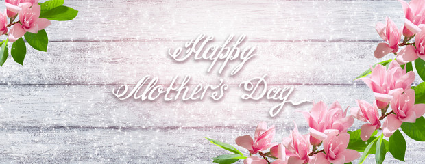 Magnolia flowers with greeting for Mother's day on background of shabby wooden planks
