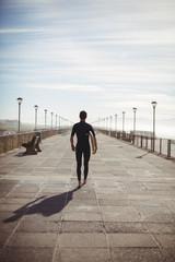 Rear view of surfer with surfboard walking on boardwalk