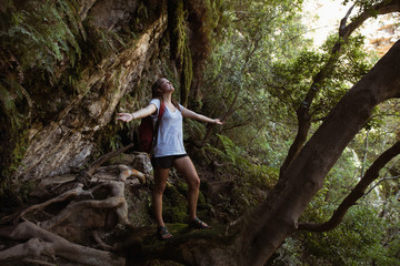Female hiker standing with her arms outstretched in the forest