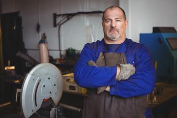 Welder standing with arm crossed in workshop