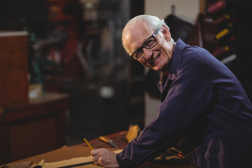 Portrait of shoemaker cutting a piece of leather
