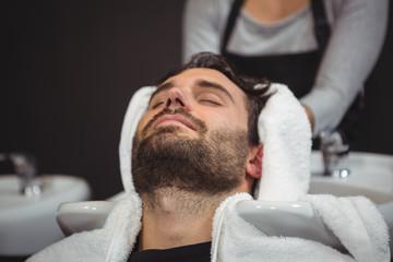 Hair stylist drying man hair with towel
