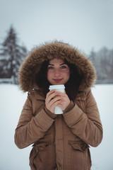 Smiling woman in fur jacket having coffee during winter
