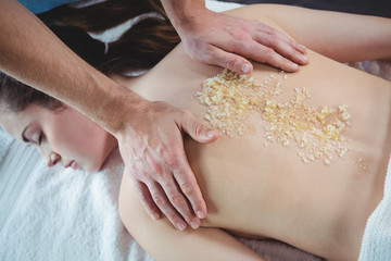 Woman receiving back massage at salon