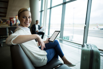 Portrait of female commuter with digital tablet sitting in waiting area