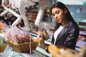 Woman selecting sausage at meat counter