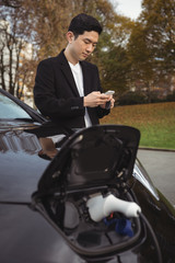 Man using mobile phone while charging electric car