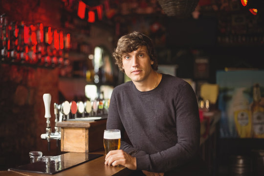 Portrait of man with a glass of beer at bar counter