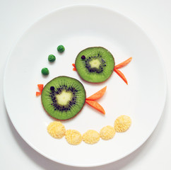 stock-photo-fish-family-parents-and-children-from-kiwi-healthy-and-fun-food-for-kids-on-white-plate-top-view