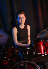 Female playing on drumset on stage