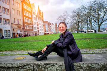 Young beautiful woman sitting in the Old Town of Cologne, Germany