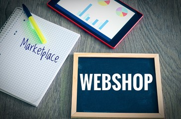 Plate with the inscription Webshop and Marketplace with a tablet Graphs and statistics and block to illustrate the increase in sales of an online shop