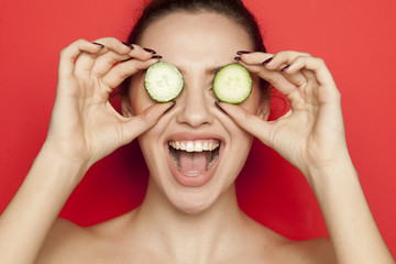 Happy young woman posing with slices of oranges on her face on red background
