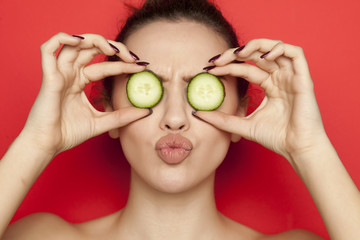 Sexy young woman posing with slices of cucumber on her face on red background