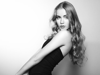 Portrait of beautiful young blonde girl in black dress. Fashion photo. Long Hair