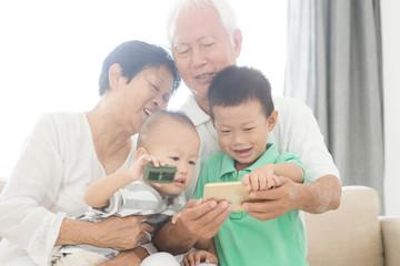 Grandparents and grandchildren selfie with smart phones