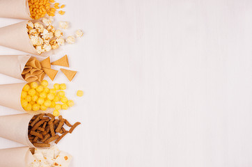Golden colorful snacks - nachos, popcorn, croutons, chips in craft paper cone as border on white wood table with copy space.