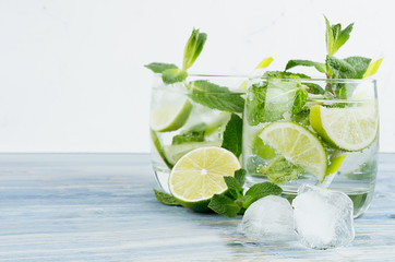 Fresh cold summer beverage gin and tonic with lime, leaf mint, straw, ice cubes, soda on light  white background.