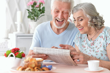 Senior couple with newspaper at home
