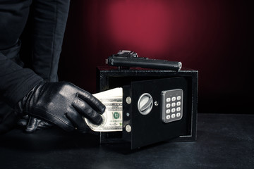 Close-up view of criminal opening safe with dollars