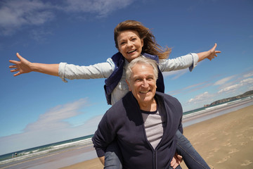Senior man giving piggyback ride to woman at the beach