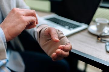 Businessman with bandaged hand.