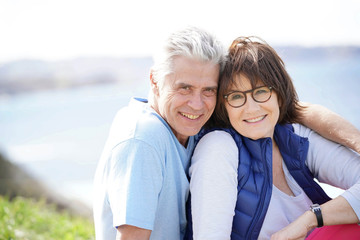 Portrait of cheerful 60-year-old couple relaxing by the sea