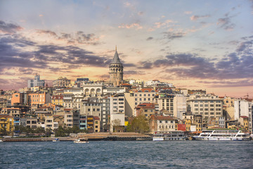 Scenery of Galata district with the famous Galata Tower over the Golden Horn, Istanbul, Turkey at sunset. Galata Tower is one of main travel attractions in the city.