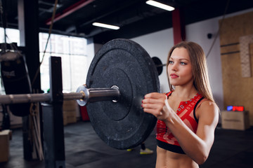 Picture of athlete girl in sports clothes with barbell
