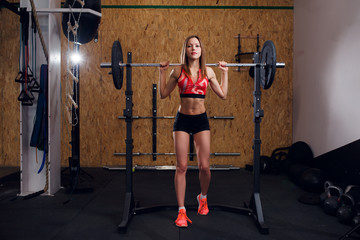 Full-length photo of young athlete in sports clothes with barbell