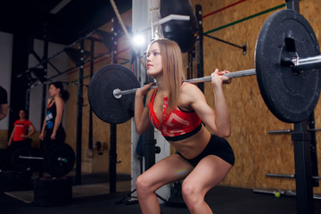 Photo of young athletic woman squatting with barbell