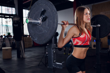 Picture of young athletic woman squatting with barbell