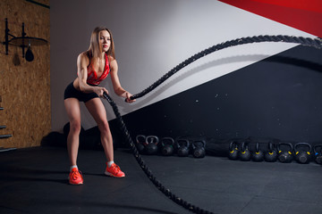 Picture of female athlete in training with two black ropes