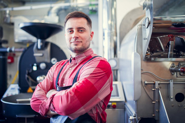 Photo of young man in apron on background of industrial coffee grinder