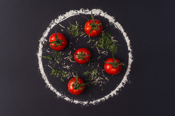 A pizza drawing on a black background made from flour and tomatoes. Concept