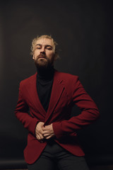 Modern businessman. Handsome young beautiful and confident bearded blond man, wearing black shirt and red jacket, standing in studio with dark background