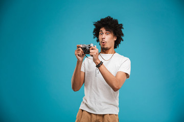 Shocked young african curly man photographer