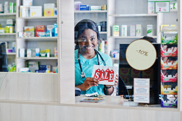 Two african american pharmacist working in drugstore at hospital pharmacy. African healthcare. Cashier holding sale.