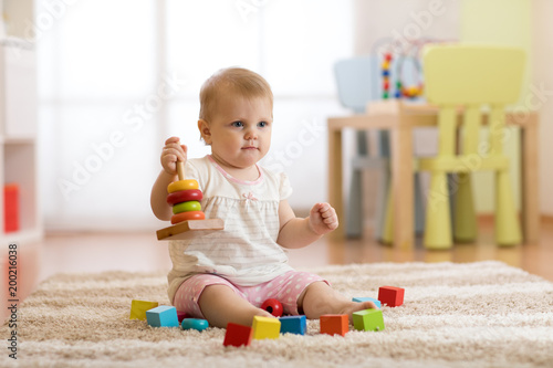 Cute Baby Girl Playing With Colorful Toys Sitting On Carpet In White
